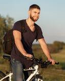 年轻人骑自行车者在木头的骑马自行车在日落 免版税库存照片