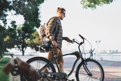 年轻人骑自行车者走与在堤防的自行车在夏天每日生活方式都市休息的概念 免版税图库摄影