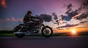人骑马在日落期间的sportster摩托车 图库摄影