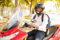 年轻人骑马工作的小型摩托车 库存图片