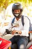 年轻人骑马工作的小型摩托车 库存照片