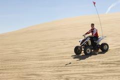 人骑马方形字体自行车在沙漠 免版税库存图片