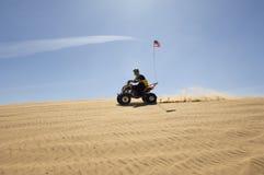 人骑马方形字体自行车在沙漠 免版税图库摄影