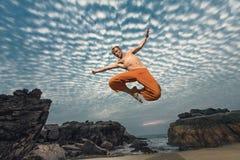 年轻人高跳跃在海滩 免版税库存照片