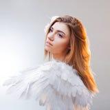 年轻人,一个天使的图象的美妙的白肤金发的女孩与白色翼的 图库摄影