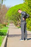 人,当跑步开始了背部疼痛时 免版税库存图片
