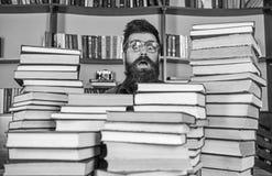 人,惊奇的面孔的书呆子在堆书之间在图书馆里,在背景的书架 书呆子概念 老师或 库存图片