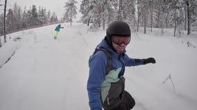 人,打扮在蓝色衣服雪板、安全帽、黄色太阳镜和卷在雪板 另一块挡雪板 股票录像