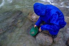 人,探油矿者摇摄金子在有水闸箱子的一条河在雨 免版税库存图片