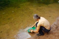 人,探油矿者摇摄金子在有水闸箱子的一条河 库存照片