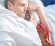 人,有一把电吉他的行家音乐家在白色床, drea上 库存照片