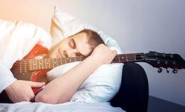 人,有一把电吉他的行家音乐家在白色床, drea上 库存图片