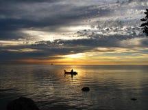 人,狗,在日出的皮船 免版税库存图片