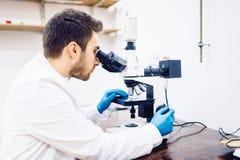 人,男性科学家,化学家与显微镜一起使用在配药实验室,审查的样品 图库摄影