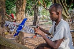人,象牙海岸- 1月31,2014 :编织传统蓝色和白色Yacouba布料的未认出的非洲人户外 免版税库存照片