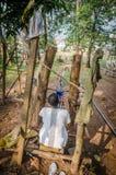人,象牙海岸- 1月31,2014 :编织传统蓝色和白色Yacouba布料的未认出的非洲人户外 免版税库存图片
