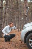人,蹲在一辆残破的汽车旁边和狂热拿着头 在秋天森林里 图库摄影