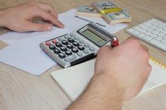 人,采取笔记、金钱和计算器在桌上 有钢笔的在一张木桌上的人和钞票 免版税库存图片