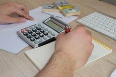 人,采取笔记、金钱和计算器在桌上 有钢笔的在一张木桌上的人和钞票 库存照片