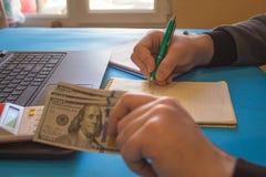 人,采取笔记 有美元的人,在桌上的现金 赢利,储款 堆美元 成功,刺激,资金流量 库存图片