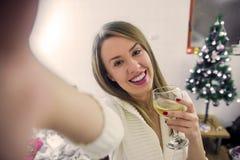 人们、假日和技术概念-美丽的性感的妇女我拍selfie照片的n白色礼服由在圣诞节的智能手机 库存照片