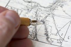 人画一张古老地图 免版税库存照片