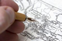 人画一张古老地图 免版税库存图片