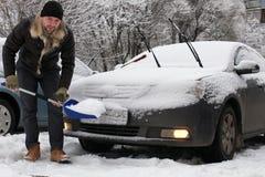 人从一辆汽车清洗雪在一个冬天早晨 免版税库存图片