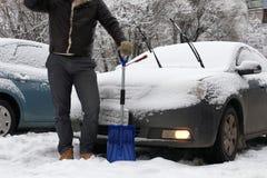 人从一辆汽车清洗雪在一个冬天早晨 免版税图库摄影