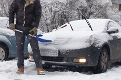 人从一辆汽车清洗雪在一个冬天早晨 免版税库存照片