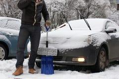 人从一辆汽车清洗雪在一个冬天早晨 库存照片