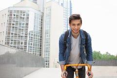 人去一辆自行车的镇在蓝色牛仔裤夹克 年轻人橙色固定自行车 免版税库存图片