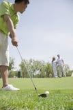 年轻人击中在高尔夫球场的一个球,男人和妇女在背景中 免版税库存照片