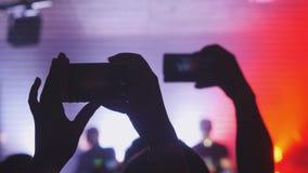 人们举行巧妙的电话和记录音乐会 拥挤集会在音乐会或夜总会 免版税库存照片