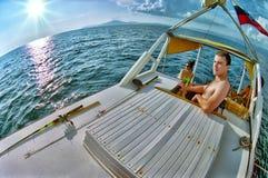人们乘在黑海的游艇航行在日落 在甲板的钓鱼竿谎言 室外夏天休闲activitities 图库摄影