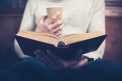 人读书和喝从纸杯 图库摄影