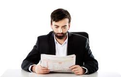 年轻人读书报纸在办公室 免版税库存照片