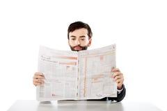 年轻人读书报纸在办公室 库存图片