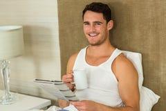 年轻人读书报纸,当拿着一杯茶时 免版税库存图片