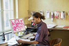 人读书纸用计算机在办公室 免版税库存照片