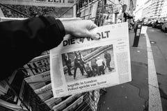 人购买在伦敦a以后死从新闻报亭的Zeit报纸 免版税库存图片