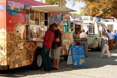 人购买饭食和快餐在食物卡车公园 图库摄影