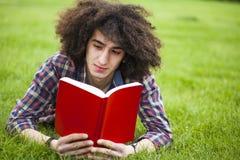 年轻人读了在草的书 库存照片