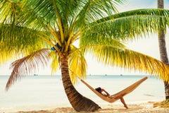 人们享受在热带沙滩的假期在背景海水和蓝天 免版税库存照片