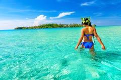 人们享受在热带沙滩的假期在背景海水和蓝天 免版税库存图片