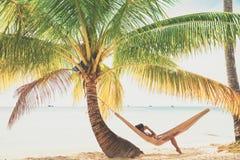 人们享受在热带沙滩的假期在背景海水和蓝天 免版税图库摄影
