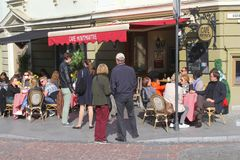 人们享用并且放松在一个晴朗的咖啡馆大阳台在老镇维尔纽斯,立陶宛 免版税图库摄影