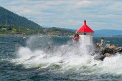 人们做旅行照片在有以后的波浪的灯塔在Frogn,挪威 图库摄影