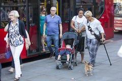 人们从公共汽车出来 有藤茎的年长母亲帮助给她的有婴儿推车的女儿,下公共汽车 免版税库存图片