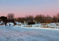 人们滑冰在一个冻湖的晚上 免版税图库摄影